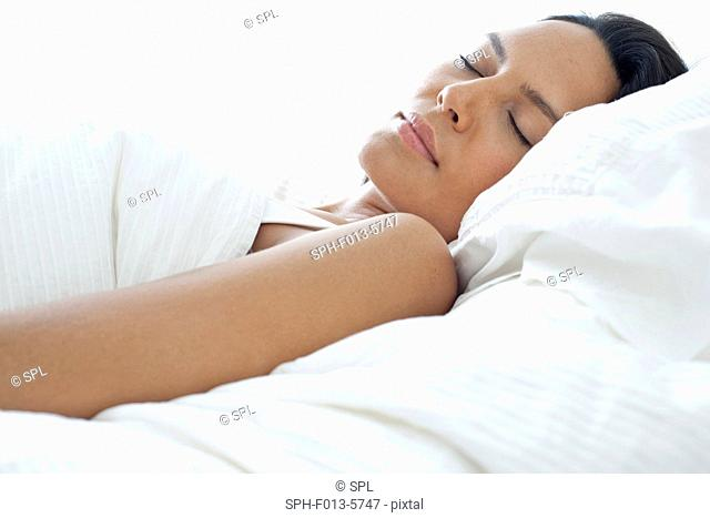 MODEL RELEASED. Young woman asleep in bed
