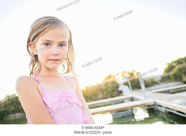 Caucasian girl standing at lakeside
