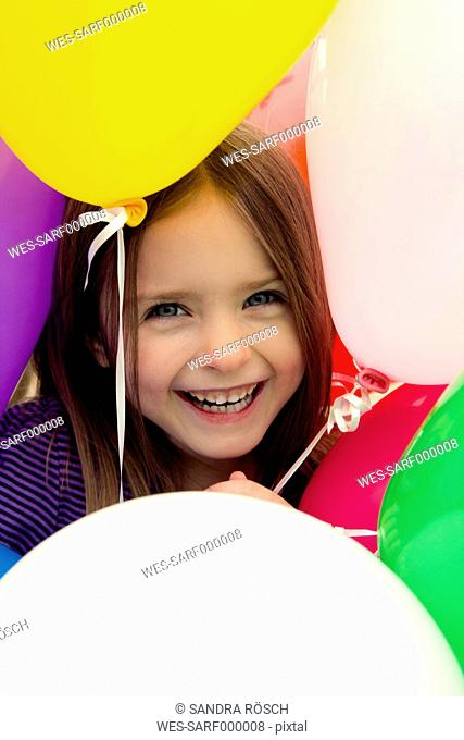 Portrait of girl in middle of balloons, smiling