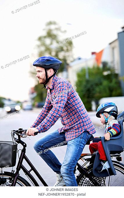 Man cycling with baby son, Vastervik, Smiland, Sweden