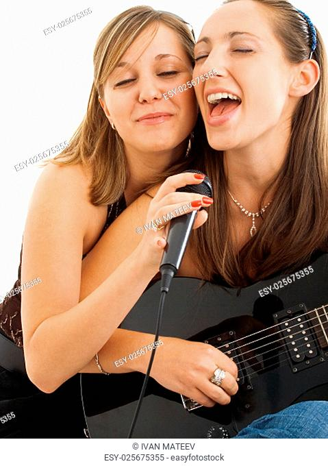 Two girls performing a song with electric guitar, isolated on white
