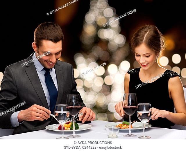 smiling couple eating at christmas restaurant
