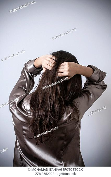 Rear view of a young woman hands on head