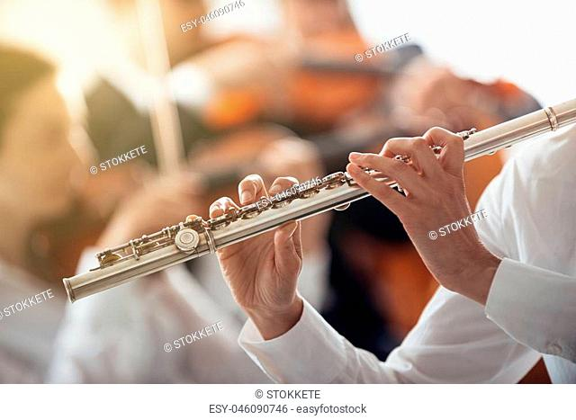 Professional female flute player performing with classical music symphony orchestra, unrecognizable person