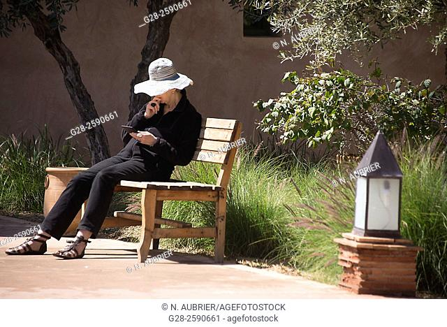 Senior woman with sun hat, sitting on a public wooden bench, reading her tablet, in a garden, Marrakech, Morocco
