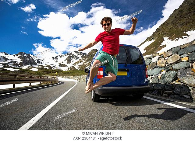 A young man jumps in the air on a mountain pass road in the Western Alps; Italy