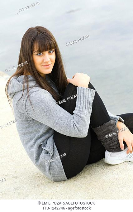 Sporting young woman is sitting on a concrete pier
