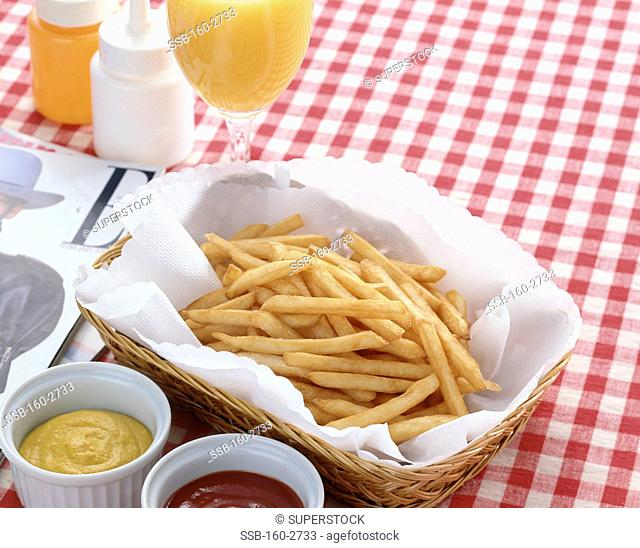 Close-up of French fries with orange juice