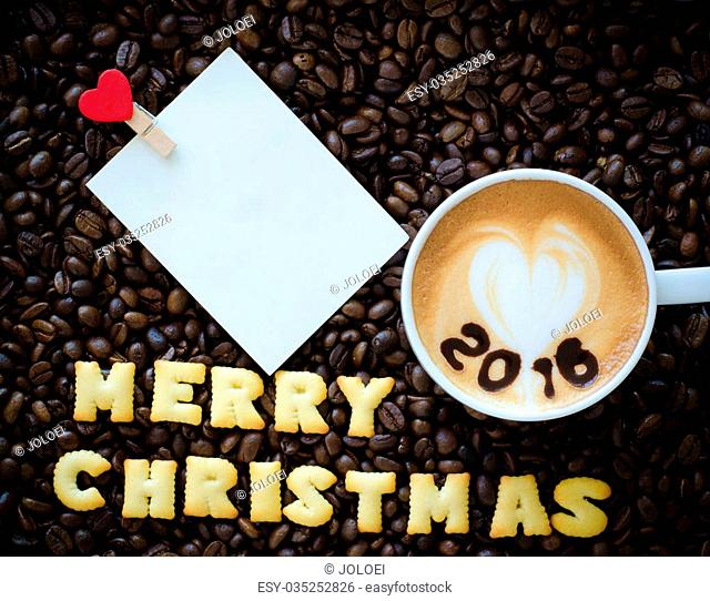 "latte art coffee and alphabet """"merry christmas"""" made from bread cookies on coffee beans background"