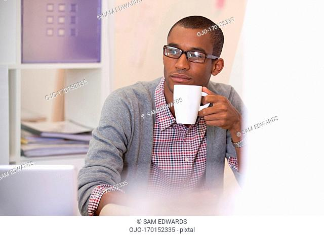 portrait of smiling businessman drinking coffee