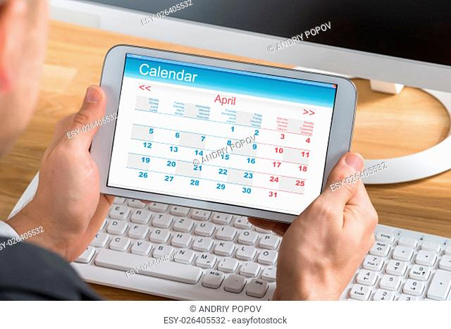 Close-up Of Young Businessman Using Calendar On Digital Tablet At Computer Desk