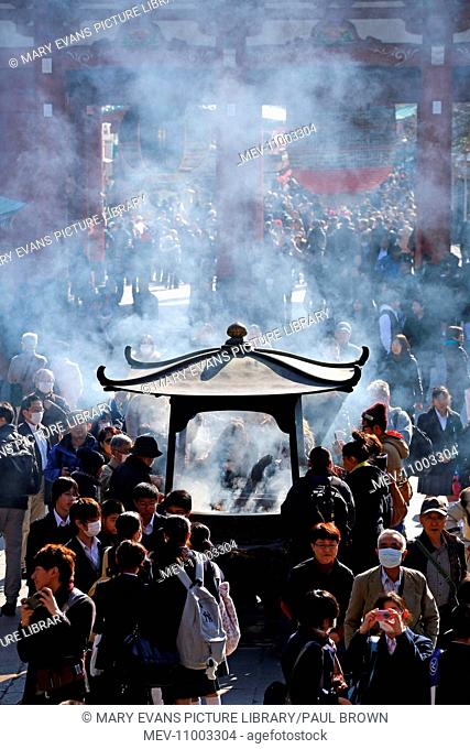 Crowds of people burning incense at the Shinto Shrine at Senso-Ji Bhuddist Temple in Asakusa in Tokyo, Japan