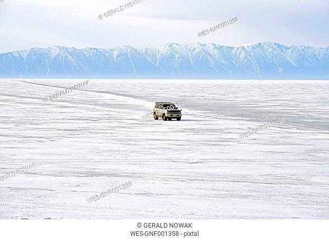 Russia, Lake Baikal, pickup truck driving on frozen lake