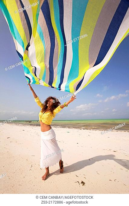 Tourist woman holding a colorful scarf at the beach, Jambiani, Zanzibar Island, Tanzania, Indian Ocean, East Africa
