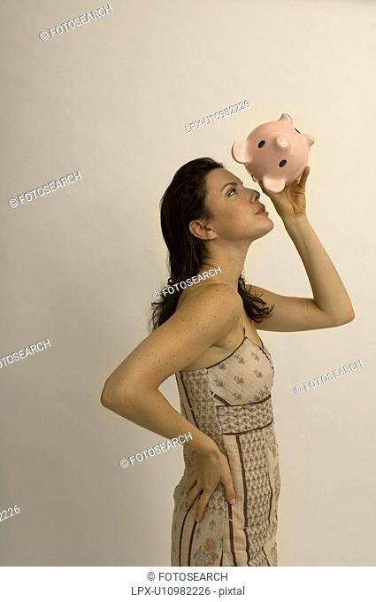 Portrait of a woman checking her piggy bank for money