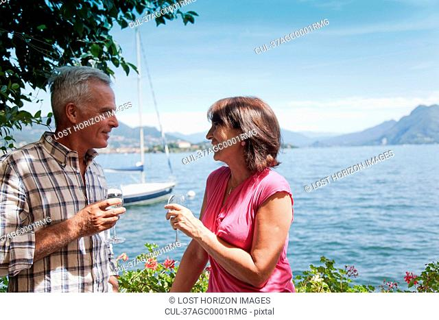 Older couple having wine by lake