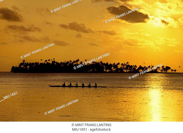 Outrigger canoe being rowed by a group of people off the shore in Bora Bora, Tahiti