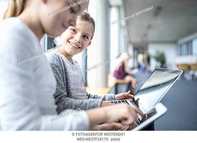 Happy schoolgirls with laptop and tablet on school corridor
