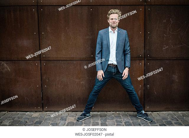 Portrait of smiling businessman standing at rusty wall