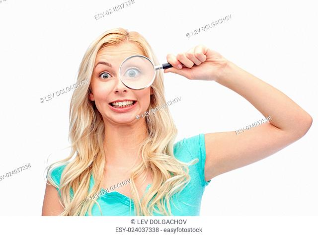 vision, exploration, investigation, education and people concept - happy smiling young woman or teenage girl looking through magnifying glass