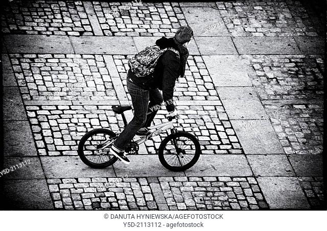 Young man - teenager - on bicycle, cobbled Cathedral square, Cadiz, Andalusia, Spain, view from above