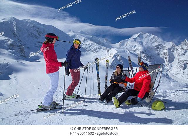 Gruppe mit Ski und Liegestuhl auf Diavolezza vor Piz Bernina