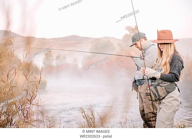 A couple fishing on a riverbank, tying the flies to the hooks for fly fishing