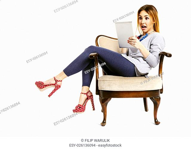 Young woman sitting on a chair watching tablet with an opened mouth very surprised and disbeliefed