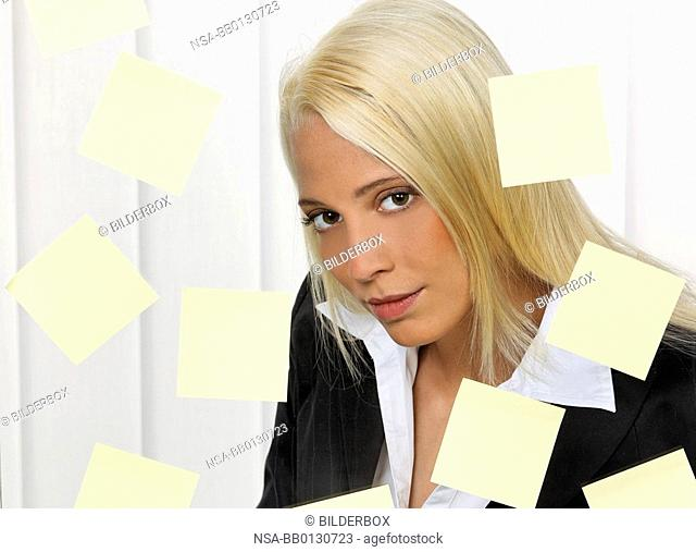 Stressed young woman with multiple tasks leaflets