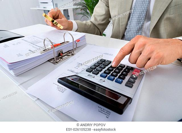 Midsection of male accountant using calculator while holding magnifying glass over bills in office