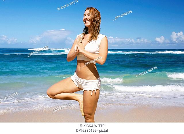 A young woman does yoga on the beach; Kauai, Hawaii, United States of America