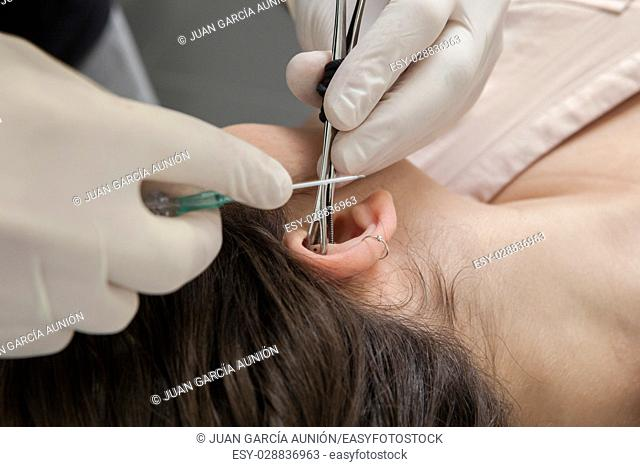 Professional making a piercing hole on ear with indwelling cannula method. Rook type. Gripping the ear