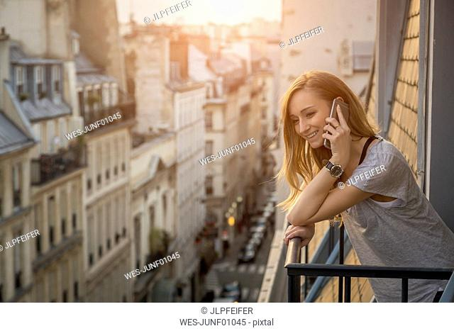 France, Paris, portrait of smiling woman on the phone standing on balcony in the evening