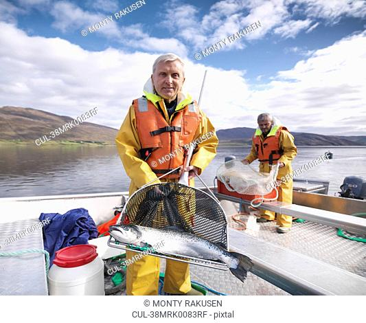 Fisherman holding salmon in net