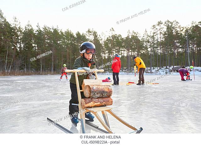 Boy learning to ice skate with kicksled on frozen lake, Gavle, Sweden