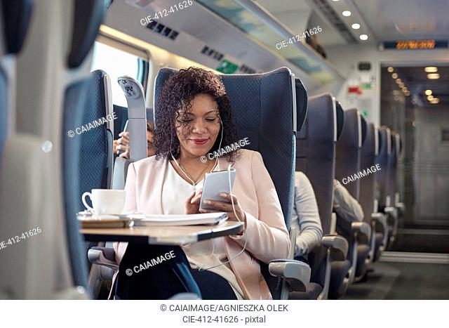 Businesswoman working and listening to music with headphones and smart phone on passenger train
