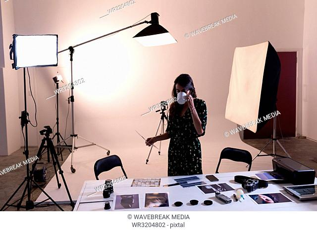 Female photographer having coffee while looking at photographs