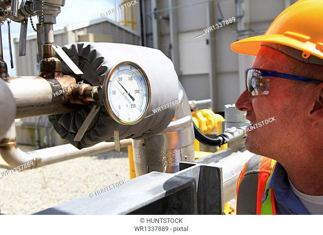 Engineer examining transducer gauge at electric power plant
