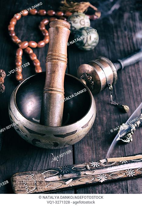 copper singing bowl and a wooden stick on a brown table, vintage toning