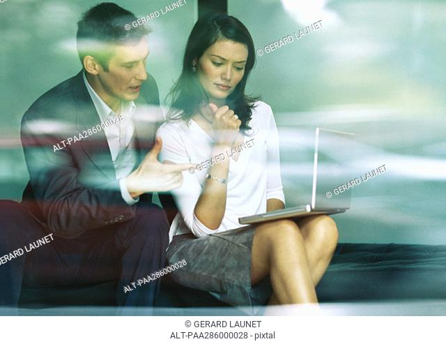 Businessman and businesswoman sitting together, looking at laptop