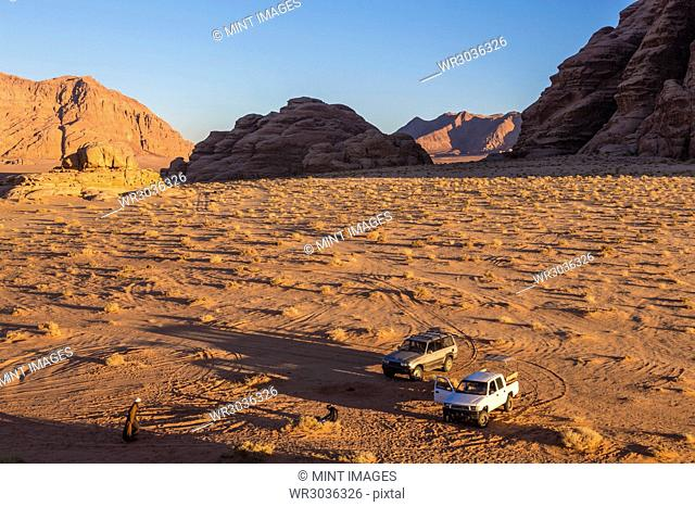 Two cars parked in desert landscape with rocks and mountains