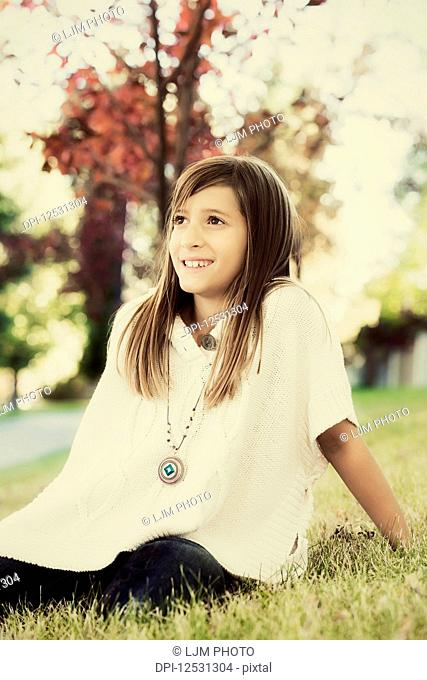 Portrait of a young girl sitting on the grass in a park in autumn; Edmonton, Alberta, Canada