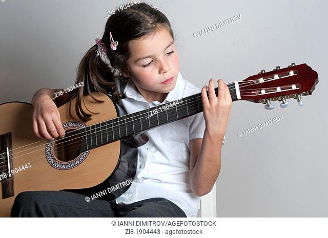 Child plays the guitar