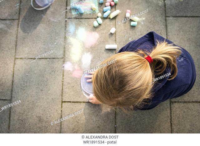 Blonde girl drawing with chalk on sidewalk, Munich, Bavaria, Germany