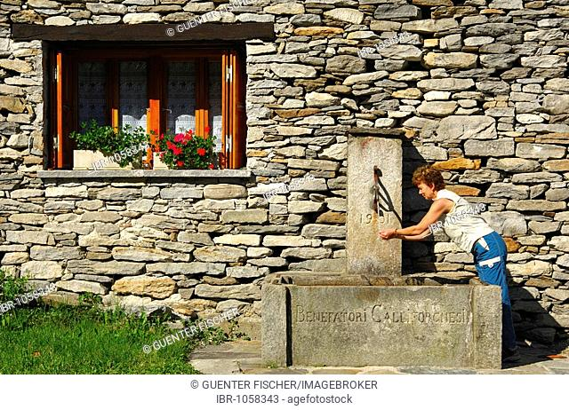 A woman drinking from a fountain inscribed with Benefatori Califorchesi, 1901, donated by emigrants from the Verzasca valley to California, Verzasca valley