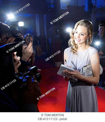 Well dressed female celebrity signing autograph and posing for paparazzi on red carpet