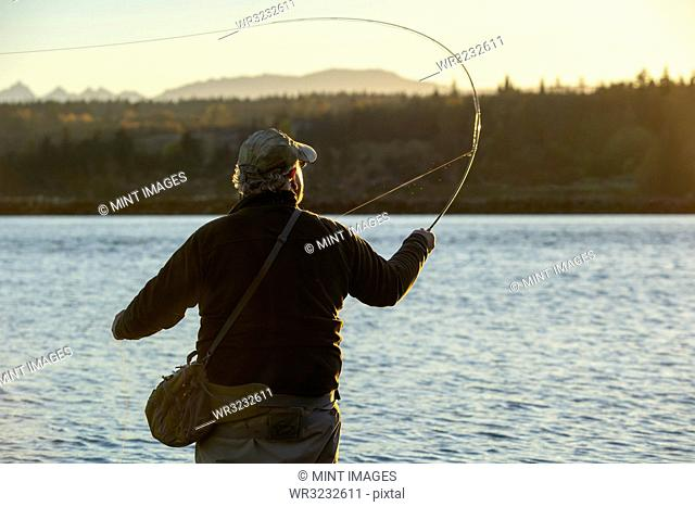 A view from behind of a fly fisherman casting for salmon and searun coastal cutthroat trout from a salt water beach
