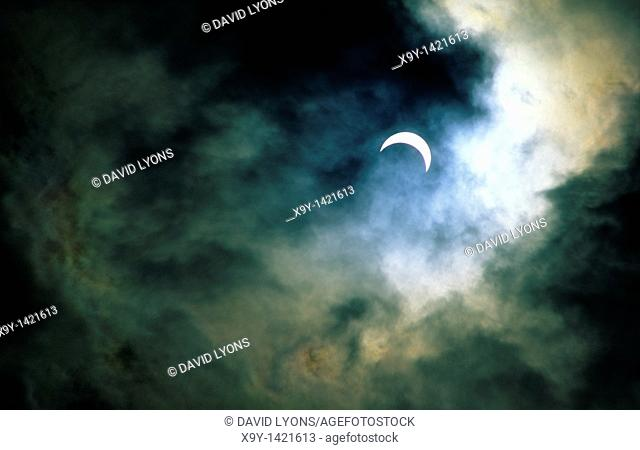 Solar eclipse  Moon passing in front of sun approaching full eclipse  Romantic atmosphere veiled by thin stormy clearing cloud