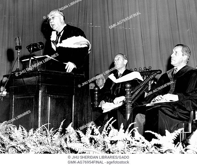 Commemoration Day 1951 at Johns Hopkins University, with humanities scholar Henry Allen Moe standing at the podium to the left giving a speech to graduating...