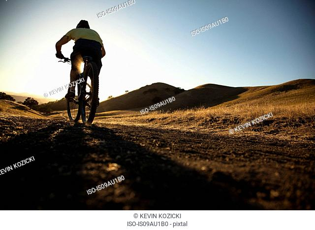 Silhouetted surface view of young man mountain biking up dirt track, Mount Diablo, Bay Area, California, USA